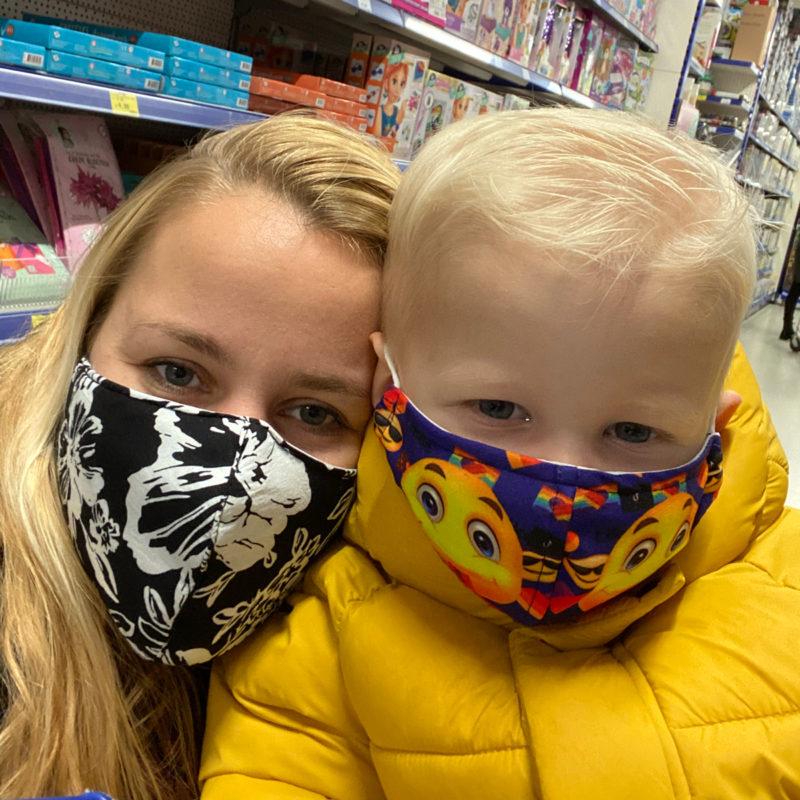 Lieneke in winkel met zoontje met mondmasker voor met smileys erop